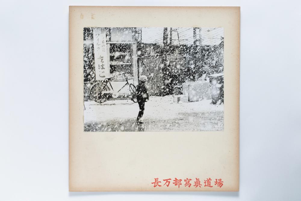 画像:<p>撮影年不詳(1962(昭和37)年以前)<br /> 本町、長万部町<br /> 舗装される前の駅前商店街通り。澤博の自宅である長万部食堂を背にして撮影されている。<br /> 澤は雪が降っている情景を好んで撮影しており、本作は澤が撮影した可能性が高い。</p>